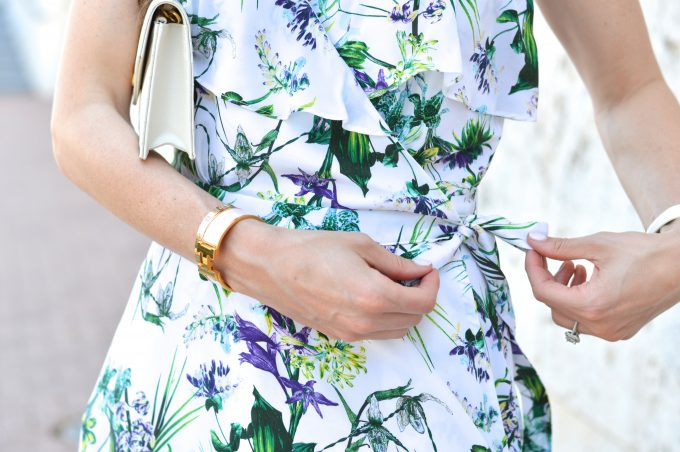 feminine details of a floral wrap dress in a summery print in shades of purple and green