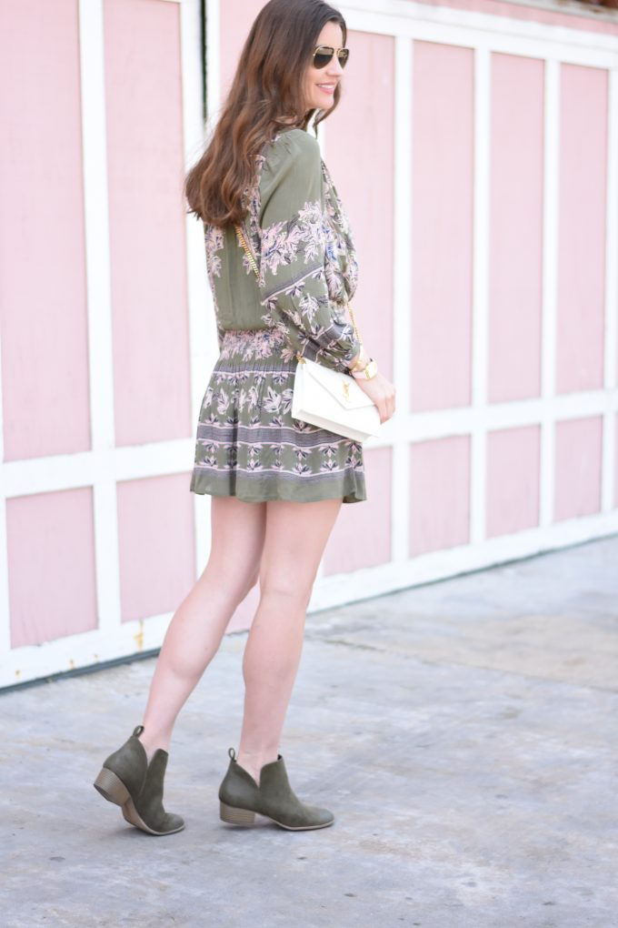 A green and blush pink boho print dress with olive green booties and a cross body bag in white