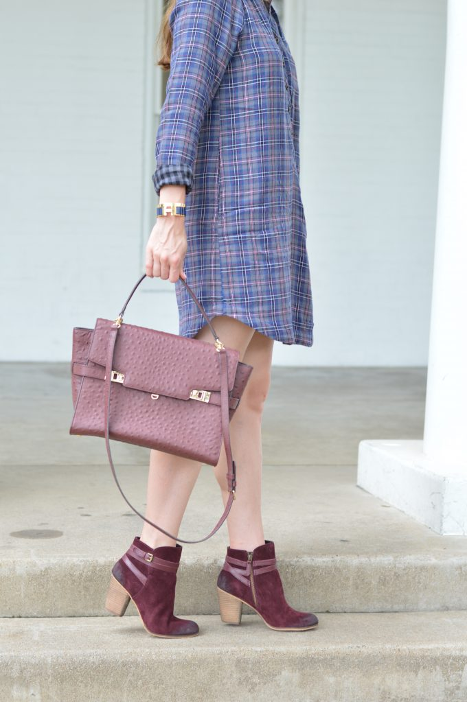 A beautiful wine colored satchel worn with a plaid shirtdress, burgundy booties and a winecolored handbag.