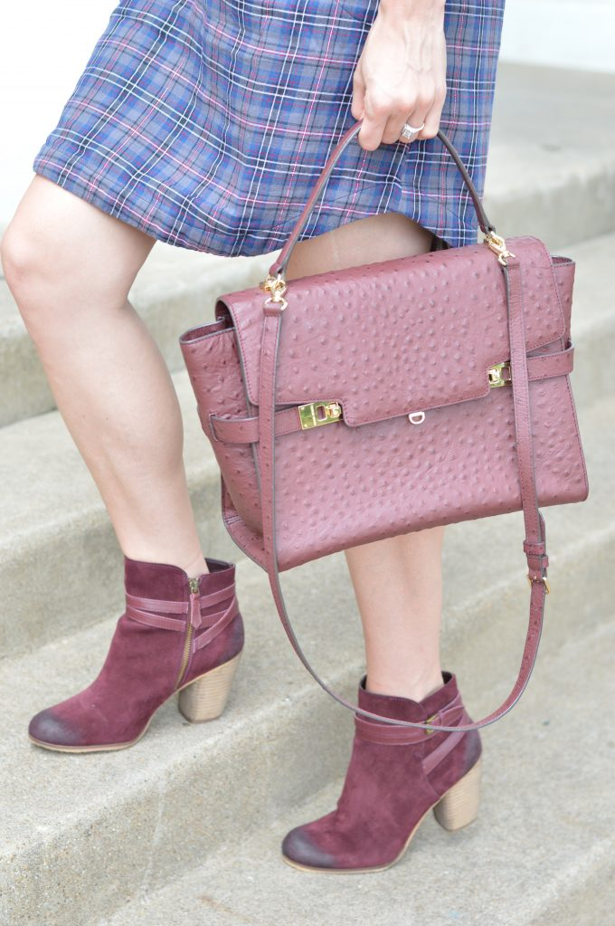 A beautiful oxblood handbag worn with great wine colored booties.