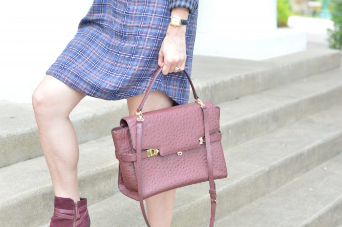 wine colored booties worn with a wine colored handbag and a plaid shirtdress that's perfect for transitioning to fall weather.