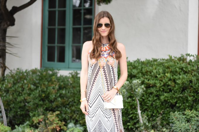 A silk midi dress in a tribal print with a YSL white crossbody bag
