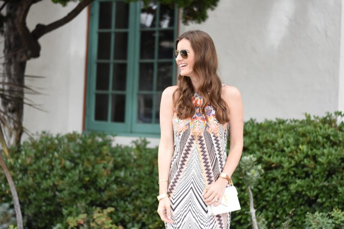 A lightweight silk midi dress with a white YSL clutch
