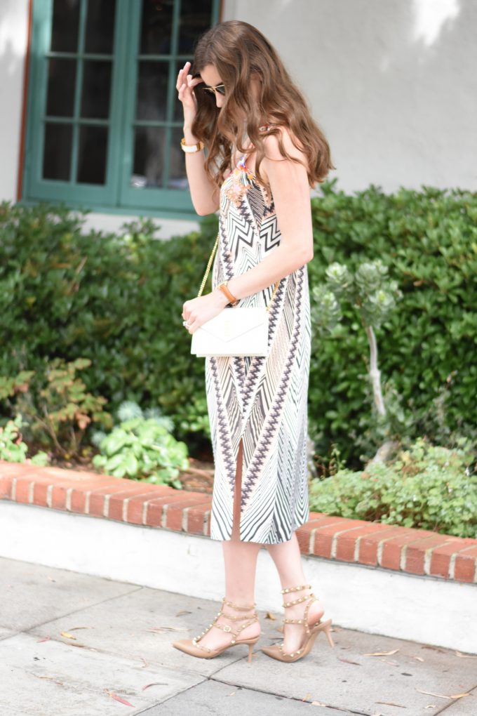 A silk print midi dress with a white YSL cross body bag and kitten heel rockstuds