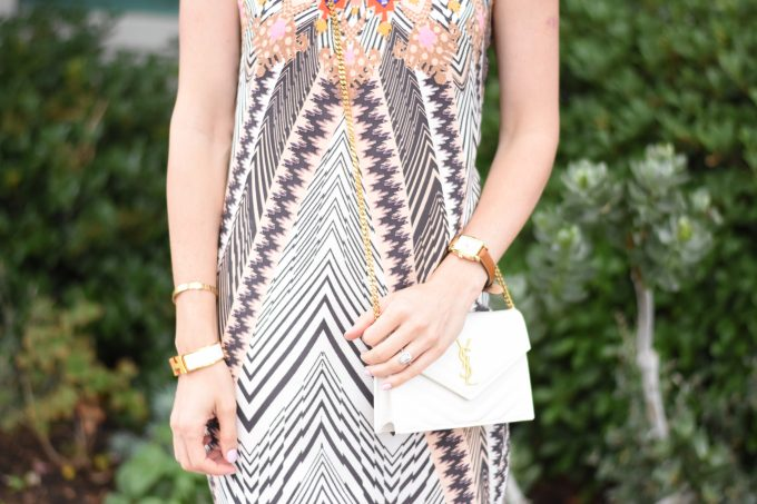 A white YSL cross body bag worn with a tribal print midi dress