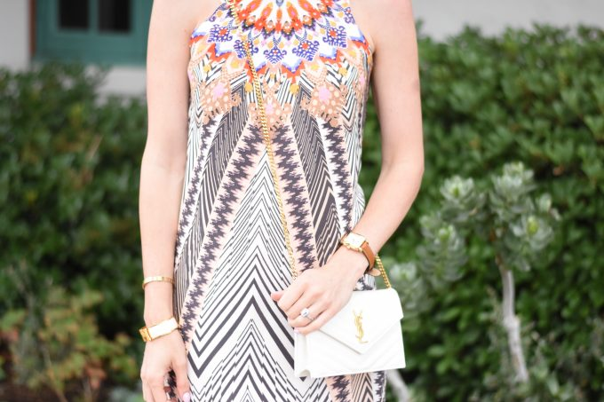 A tribal print dress with a white YSL crossbody bag