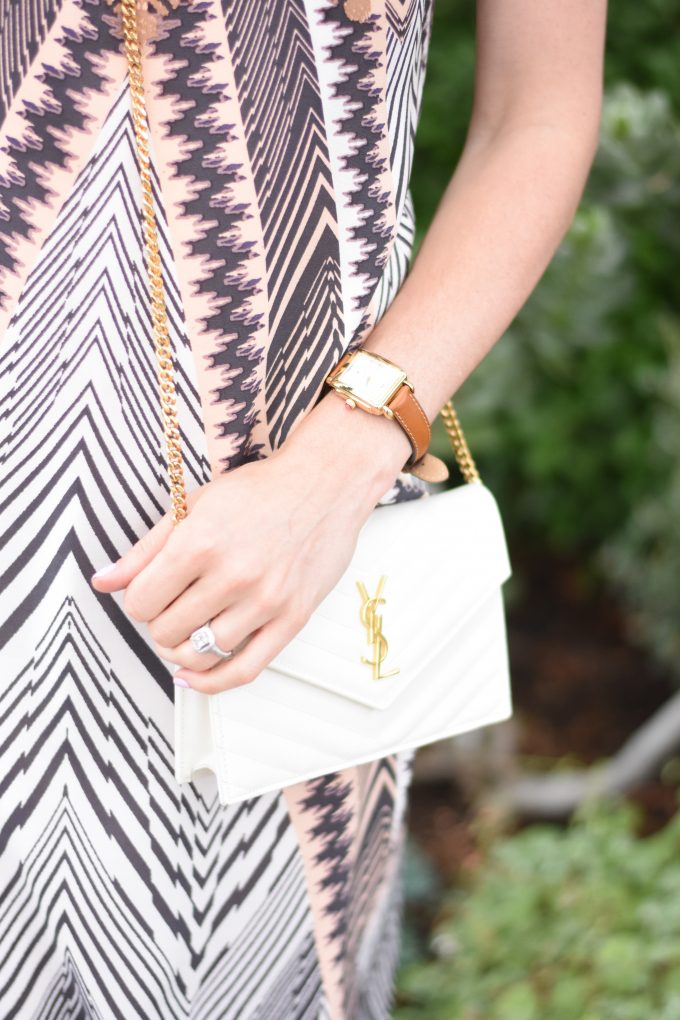 A white YSL crossbody bag and a ladies gold watch with strap in saddle brown.