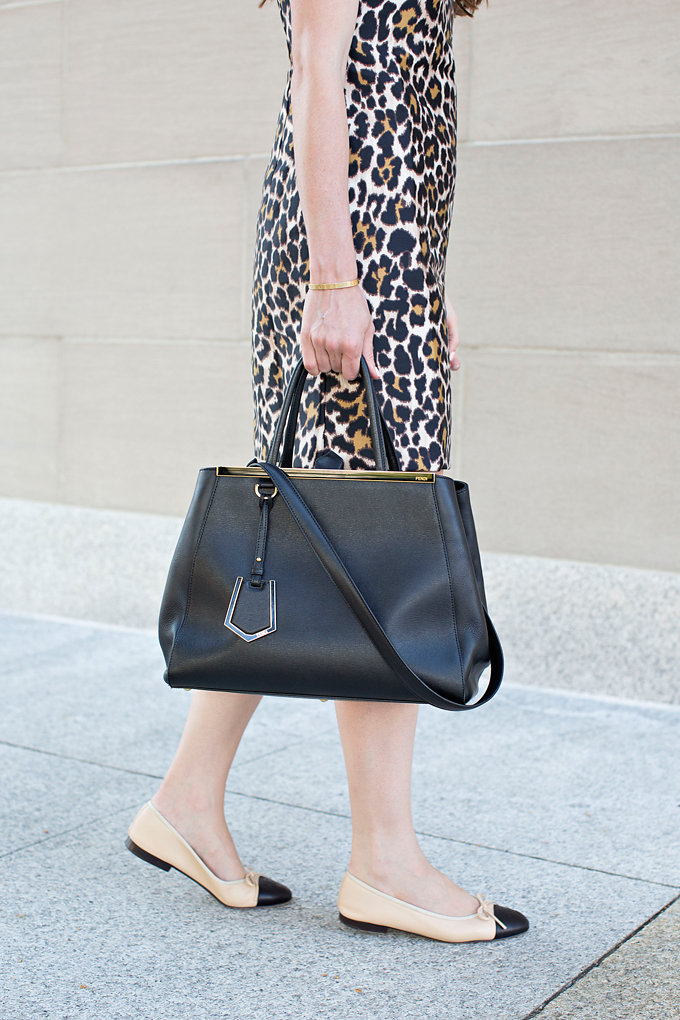 A leopard print shift dress worn with two tone cap toe chanel flats and a black tote bag