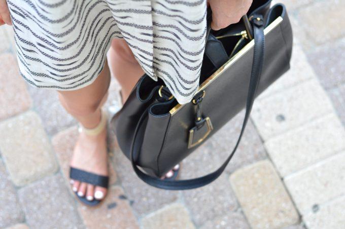 Black and ivory print mini dress with black handbag