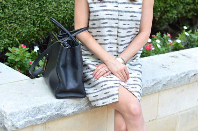 A close up detail of a balck and ivory print shirtdress and a black handbag