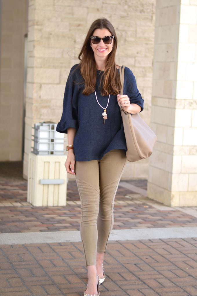 An oversized navy blue weater with tan moto pants.