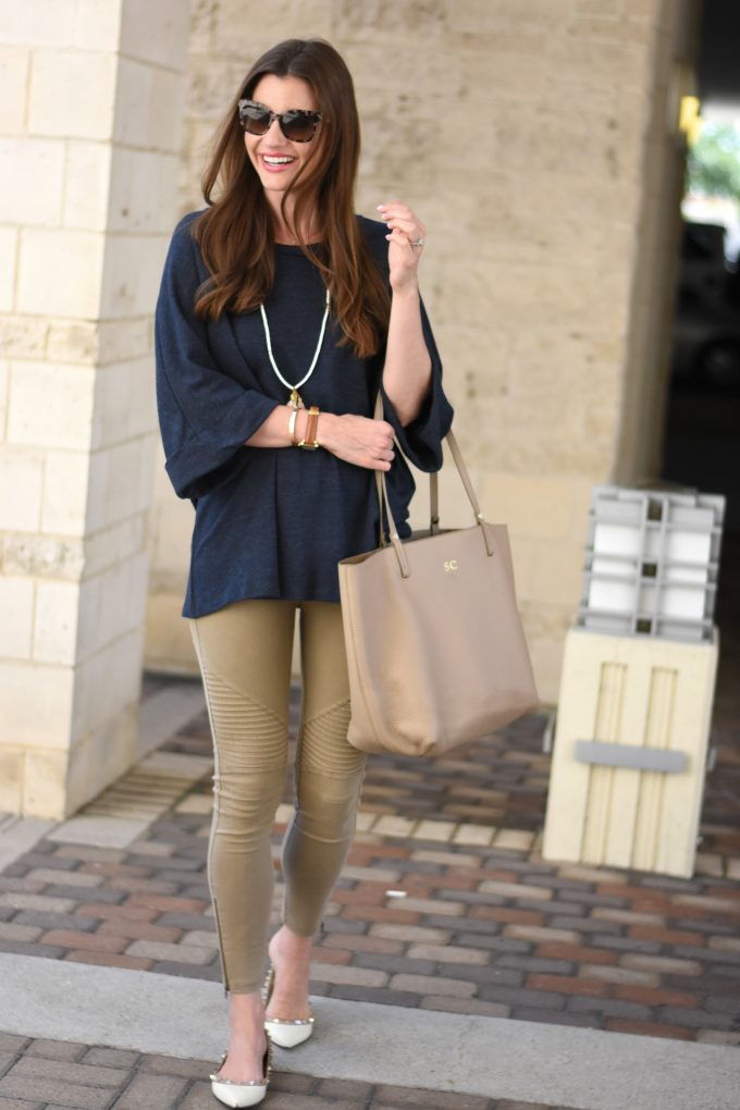 A young woman wearing a navy blue oversized sweater with tan moto pants and a tassel necklace, carrying a monogrammed shopping tote.