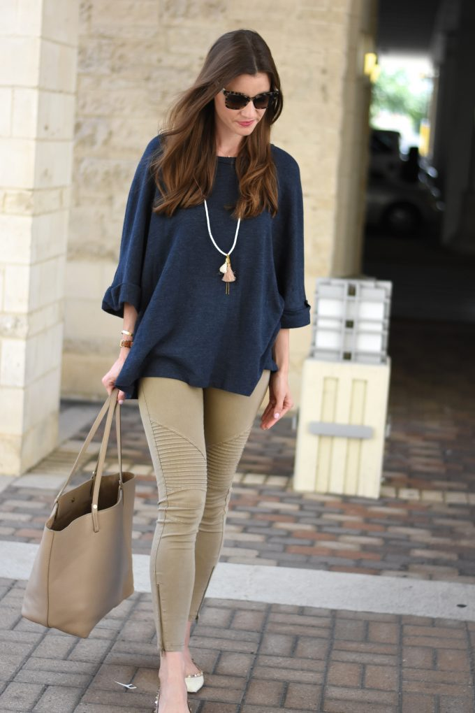 A cute navy blue oversized sweater with a tassel necklace.