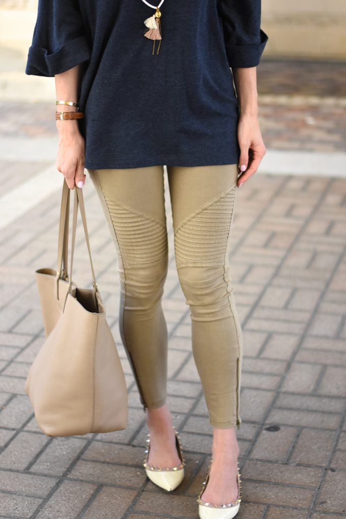 A navy blue oversized sweater with a tassel necklace and tan monogrammed shopping tote.