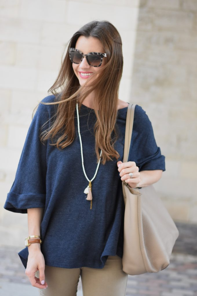 A young woman wearing Prad tortoise shell sunglasses and a tassel necklace with a navy blue oversized sweater.