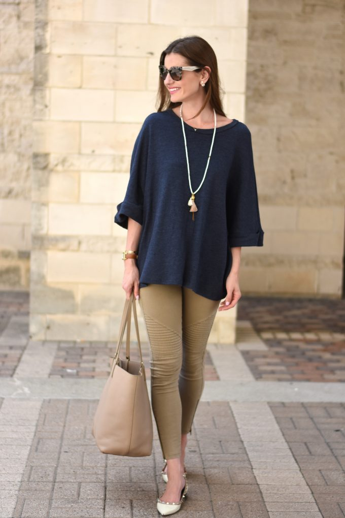 A young woman wearing a navy blue oversized sweater with a tassel necklace and a tan shopping tote.