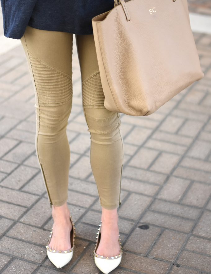 A pair of cute moto style pants with zippers at the ankles, worn with a monogrammed tan shopping tote and rockstud flats.