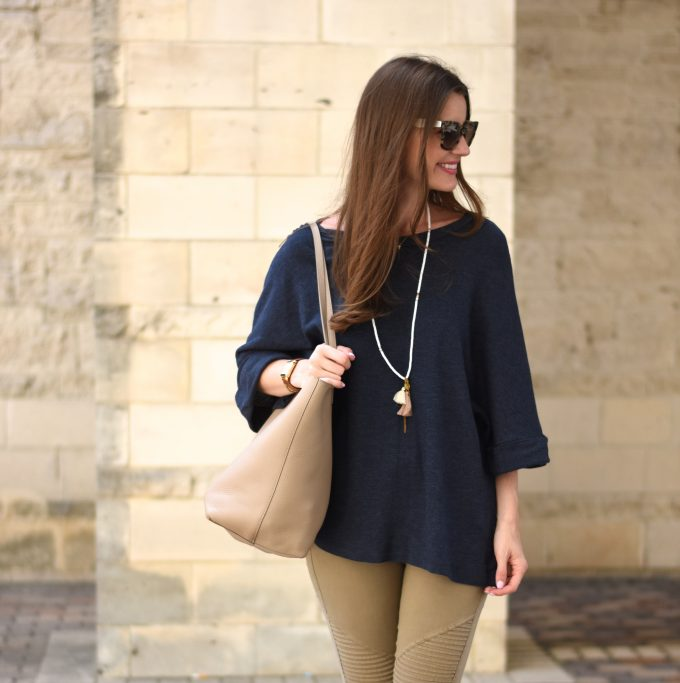 A cute oversized navy sweater wit a tan tote bag and a tassel necklace.