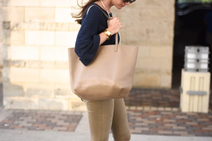 A tan shopping tote with monogram, worn with a navy short sleeve sweater.