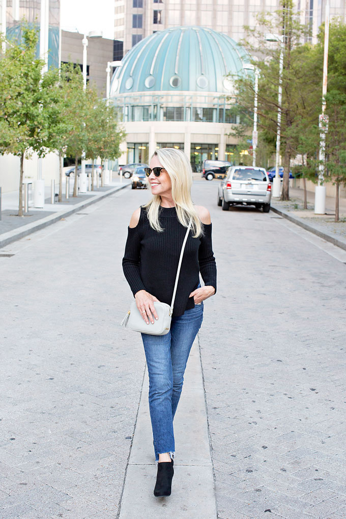 An urban chic look with frayed hem jeans, a black cold shoulder sweater and black suede wedge booties.