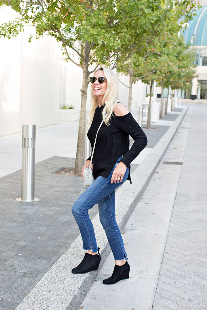 A black cold shoulder sweater and jeans with frayed and uneven hem worn with black suede wedge booties