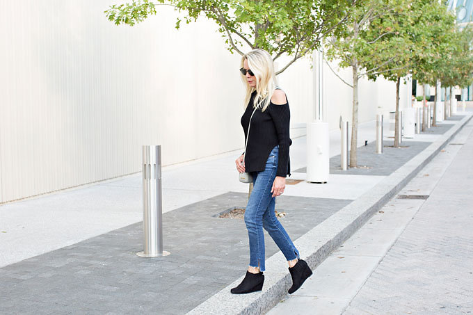 Denim with an uneven frayed hem with a black cold shoulder sweater and black wedge booties.