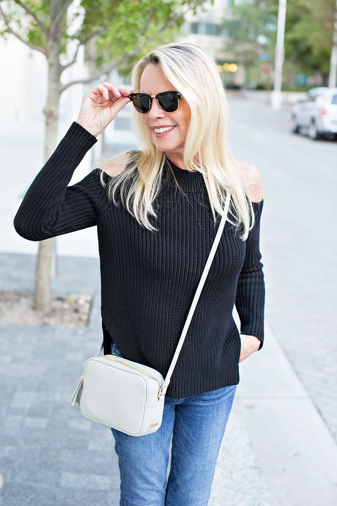 Black clubmaster sunglasses, black cold shoulder sweater and a grey monogrammed cross body bag.