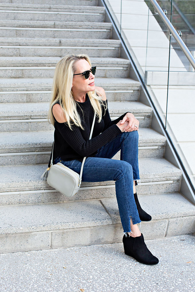 Jeans with a frayed hem and black wedge suede booties worn with a grey monogrammed cross bodu bag.