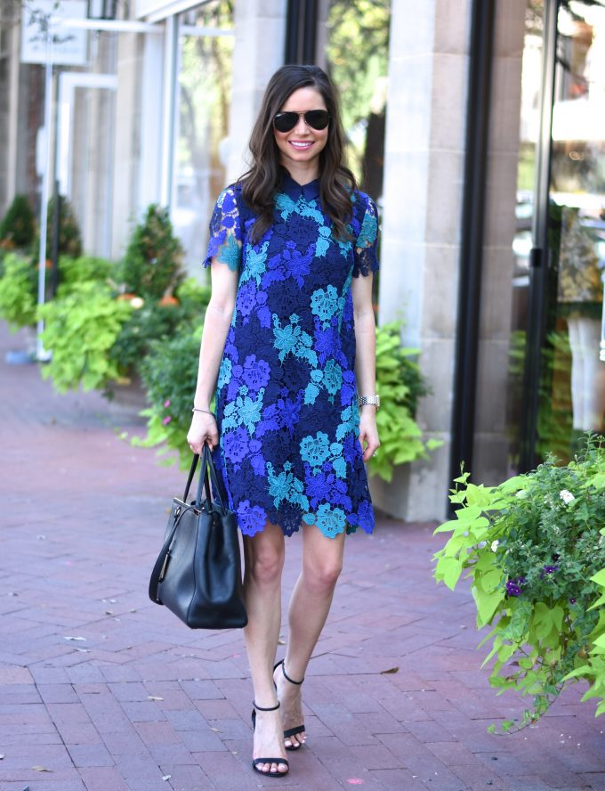 blue lace dress with black tote bag and black heeled sandals