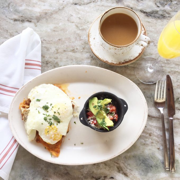 a plate of huevos rancheros, a cup of coffee, mimosa