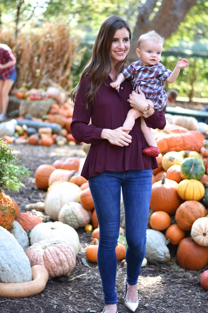 baby and mother in a pumpkin patch