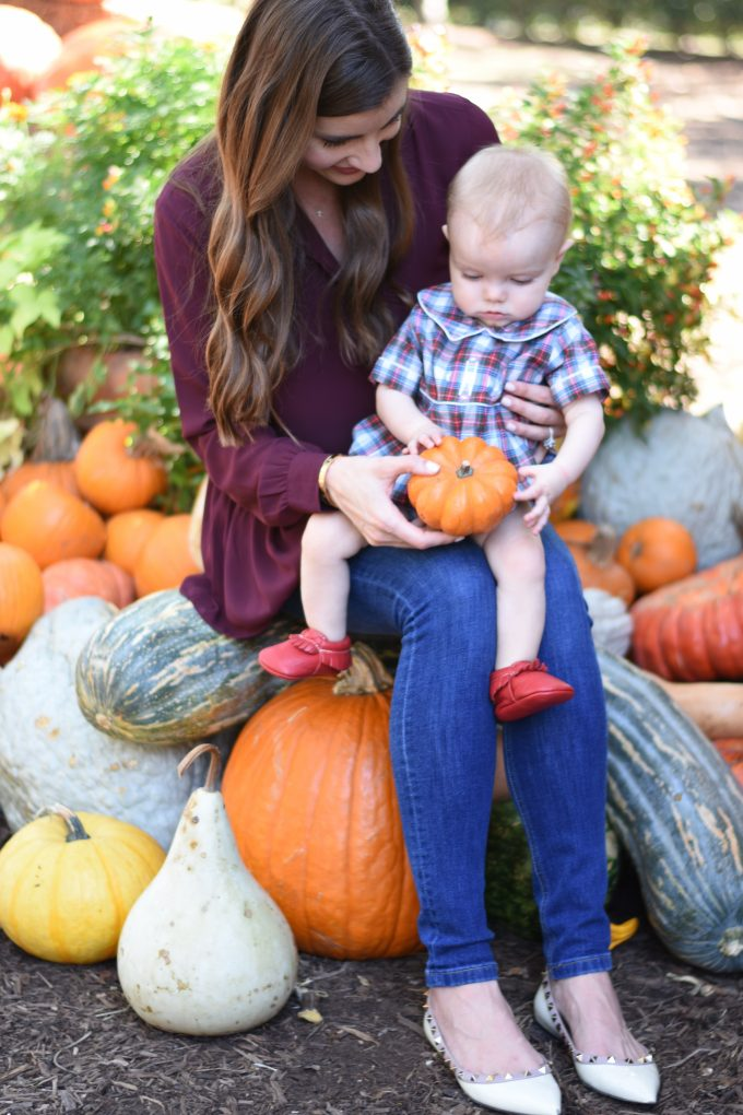 baby sitting on mother's lap looking at a miniature pumpkin