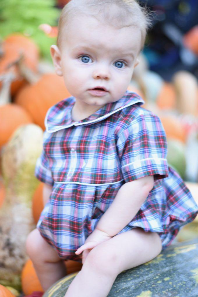 nine month old baby sitting on a pumpkin