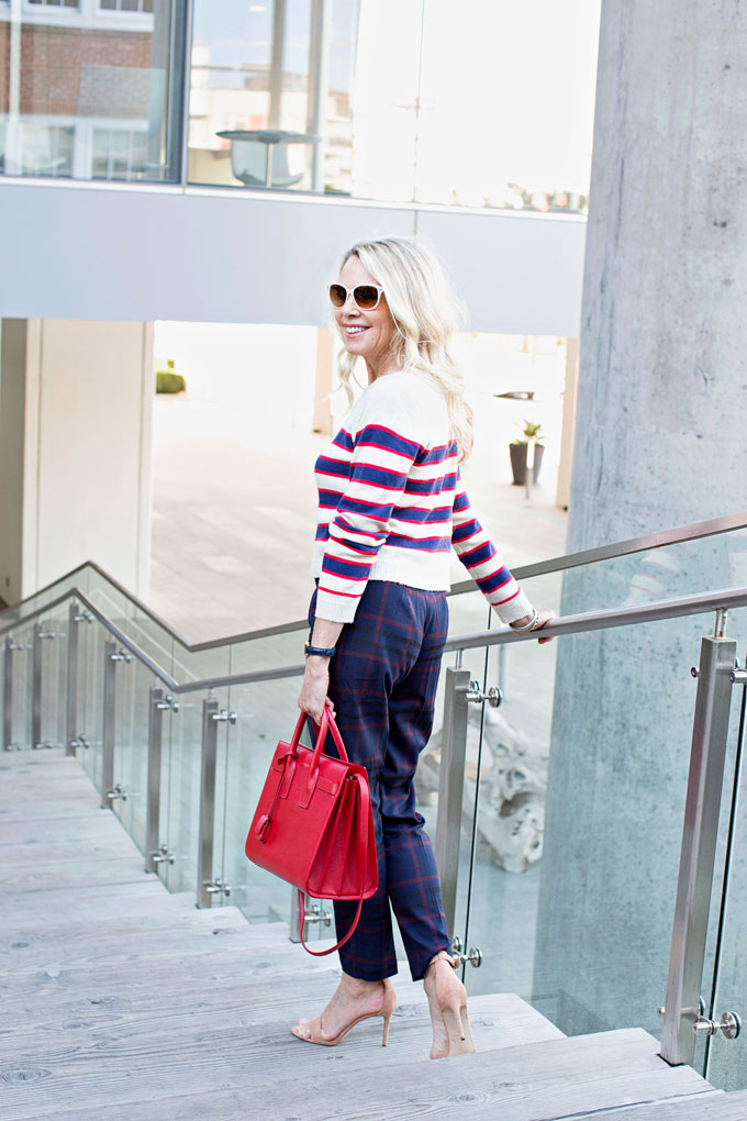 mixing prints with a striped cropped sweater and plaid pants, red handbag