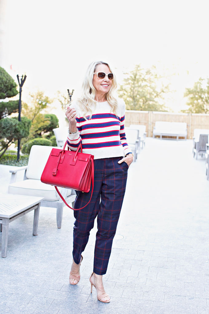 striped sweater with plaid pants and red handbag
