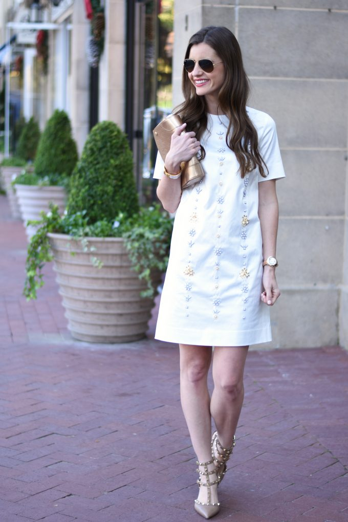 winter white party dress with embellishments on front, neutral heels, gold clutch