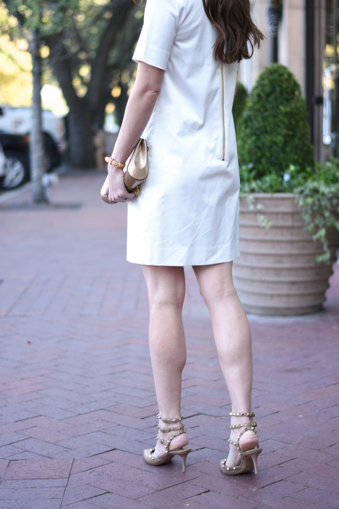 white dress with exposed gold zipper downt he back