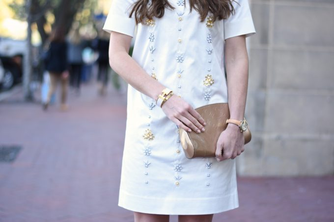 white party dress with embellishments on the front, gold clutch