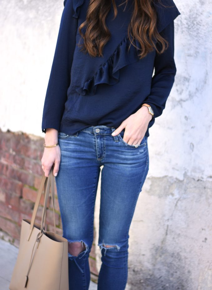 navy blue ruffle top with distressed jeans and beige tote