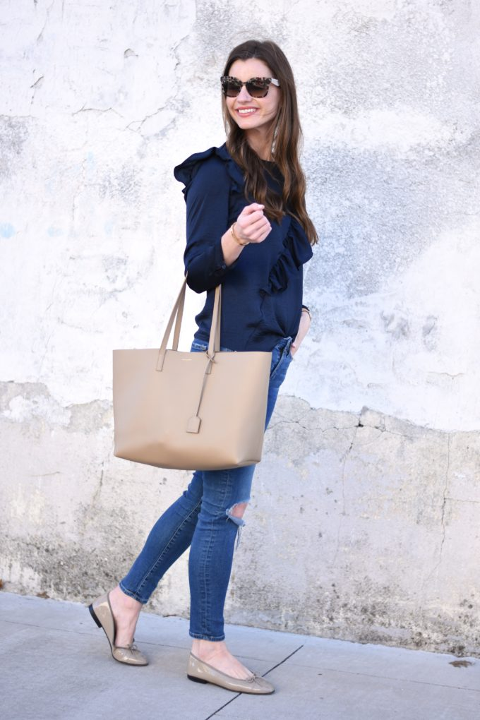 navy blue ruffle top, beige tote bag and distressed jeans