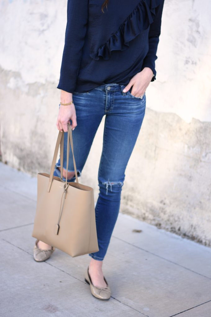 distressed jeans and a beige tote bag with nude patent ballet flats