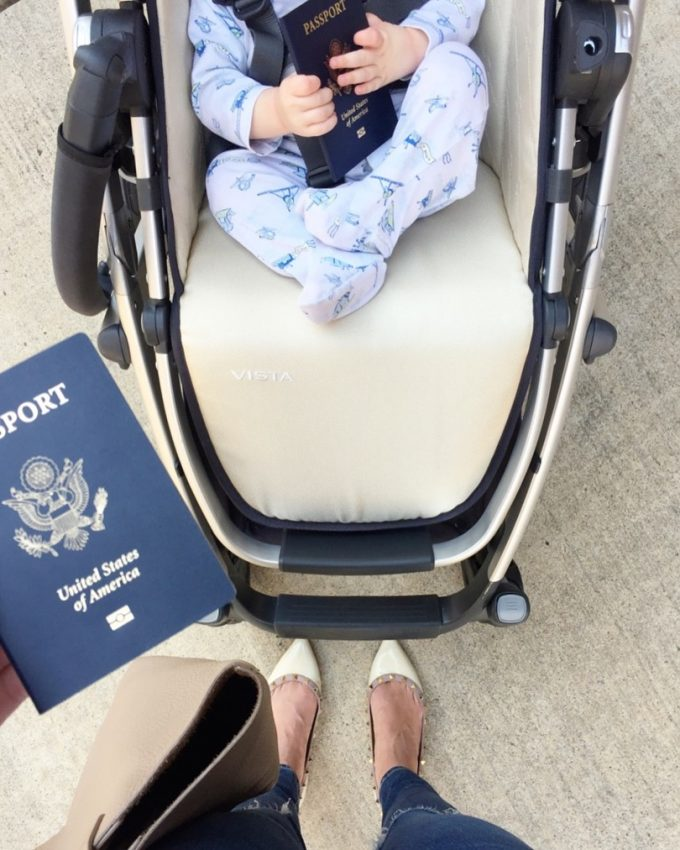baby holding passport in stroller