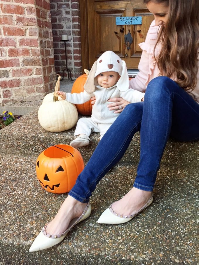 baby in puppy costume sitting by pumpkins
