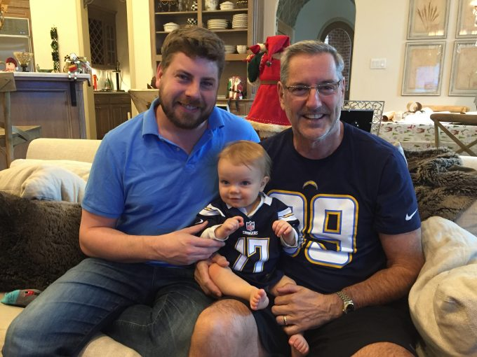 Two men holding a baby in game day jerseys