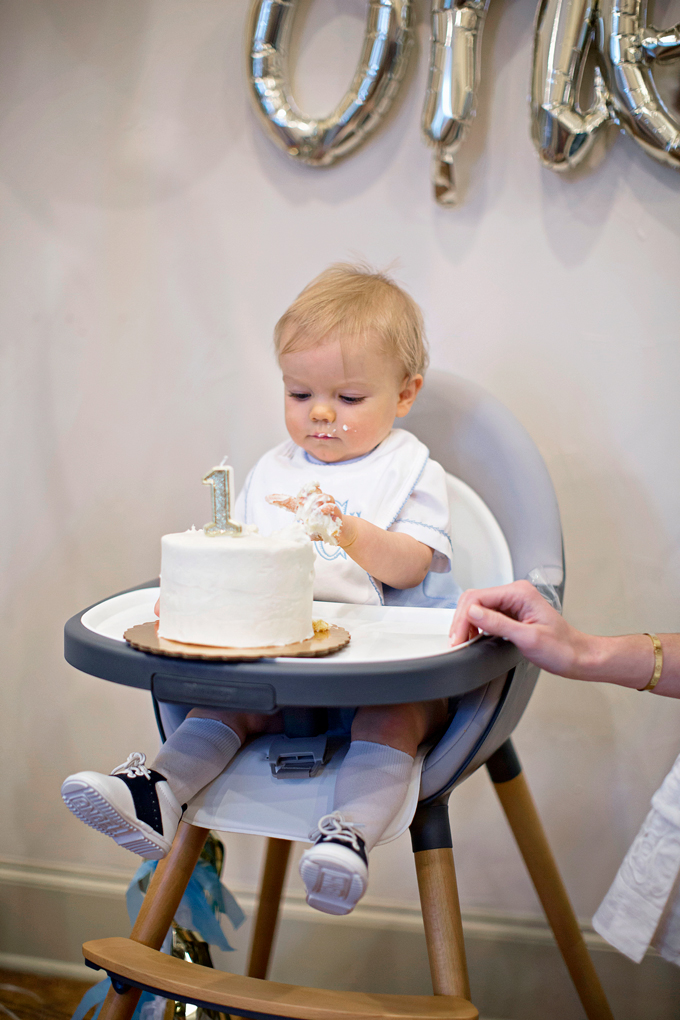 baby eating cake at first birthday party