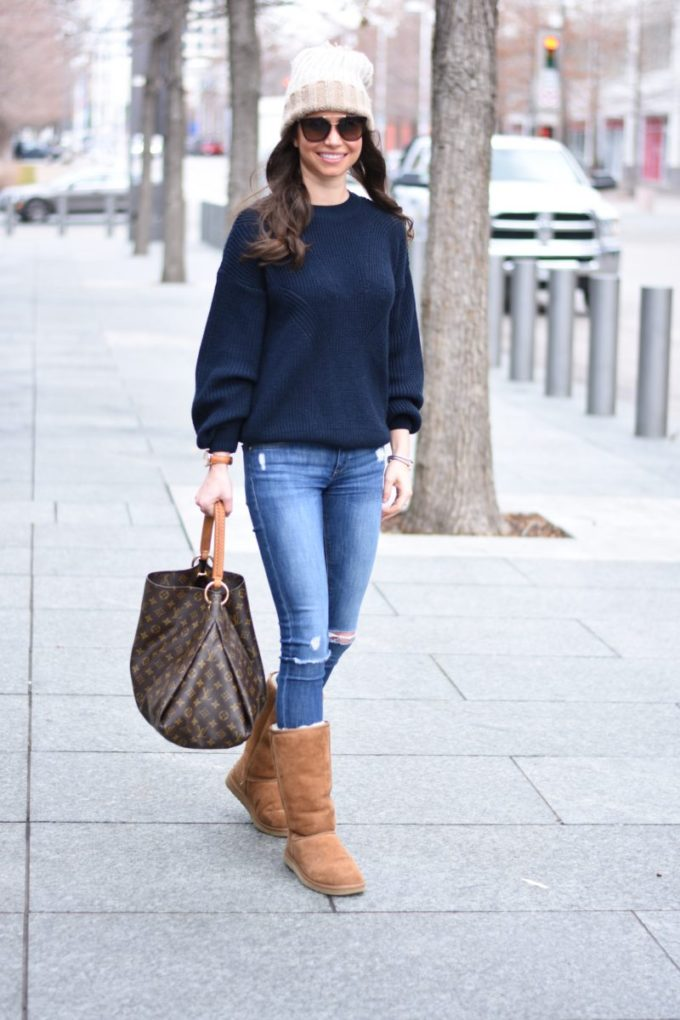 pom pom beanie with a navy oversized sweater and distressed jeans
