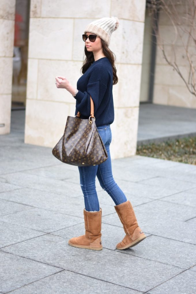 pom pom beanie with a navy blue sweater and brown ugg boots