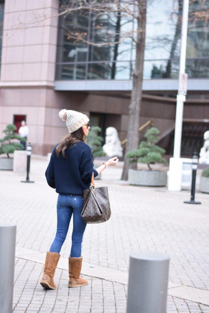 woman crosssing the street iwearinf a pom pom beanie