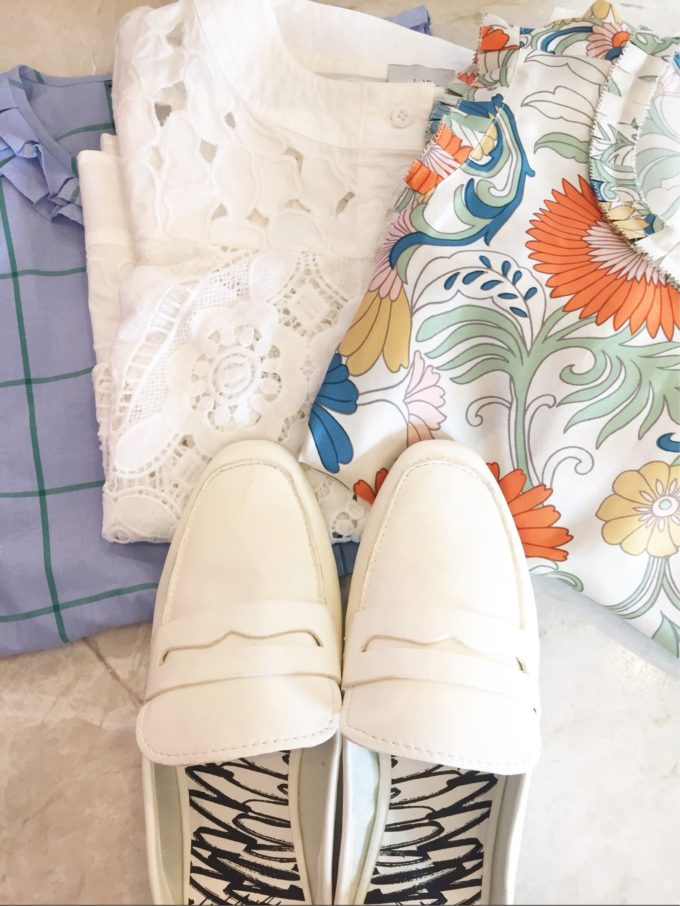 three tops and a pair of white mule loafers