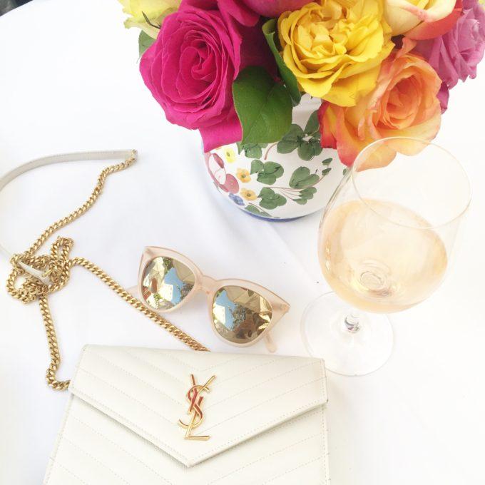 flowers, rosé wine, sunglasses and white handbag